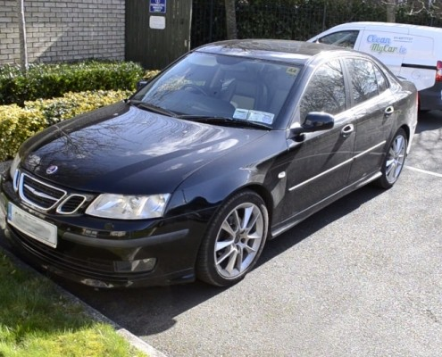 a black saab in a driveway that has been cleaned